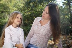 Conversation mother and daughter in the autumn park. Breathing fresh air at the weekend Royalty Free Stock Image