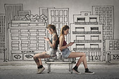 Conversation in the open air. Women sitting in a pictorial landscape looking their respective mobile Royalty Free Stock Image