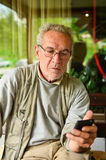 Conversation is over. Aged man has just hung up, looking at the mobile phone after some bad news Royalty Free Stock Images