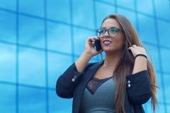 Conversation parlante de dame de succès de téléphone mobile de femme d'affaires à l'extérieur du bâtiment Images stock