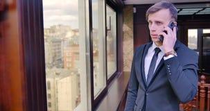 Conversation téléphonique d'homme d'affaires Un jeune homme se tient dans un costume gris dans le bureau près de la fenêtre et pa clips vidéos