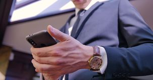 Conversation téléphonique d'homme d'affaires Un jeune homme se tient dans le costume dans le bureau près de la fenêtre et met le  banque de vidéos