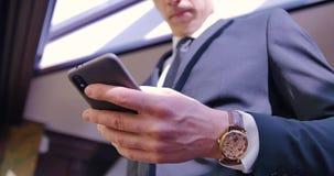 Conversation téléphonique d'homme d'affaires Un jeune homme se tient dans le costume dans le bureau près de la fenêtre Fermez-vou clips vidéos