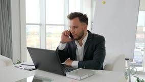 Conversation téléphonique de jeune patron dans le bureau moderne, homme d'affaires réussi Works sur l'ordinateur portable à l'Int banque de vidéos