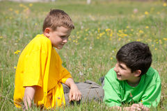 Conversation of two boys on the grass. Two boys are having a conversation outdoors Royalty Free Stock Photos