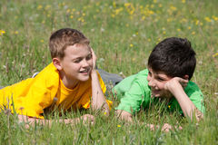 Conversation of two boys outdoors. Two boys are having a conversation outdoors on the grass Stock Photo