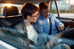 Conversation of business colleagues in driving car Royalty Free Stock Image