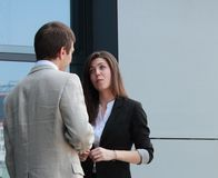Conversation between two business persons. Businessman and businesswoman having a small conversation outside the office building Royalty Free Stock Photos