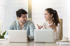 Conversation between two colleagues or business partners sitting. Business people talking during meeting sitting at the office desk using laptops, male and Royalty Free Stock Photography