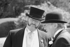 Conversation between two gentlemen with bowler hats in English style in the park Beaulieu in black and white. royalty free stock photography