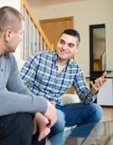 Conversation between two men indoor. Positive conversation between two adult handsome men indoors Royalty Free Stock Image