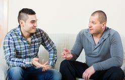 Conversation between two men indoor. Positive conversation between two adult smiling handsome men indoors Royalty Free Stock Image