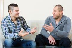 Conversation between two men indoor. Positive conversation between two adult smiling male friends indoors Stock Photos