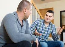 Conversation between two men indoor. Positive conversation between two smiling male friends indoors Royalty Free Stock Images