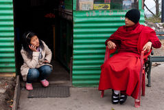 Conversations. A Buddhist student monk is talking with a young lady shopkeeper at the nearby shop of Rumtek Monastery, Sikkim, India Stock Image