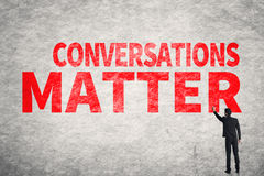 Conversations Matter. Asian business man write words on wall, Conversations Matter Royalty Free Stock Photo
