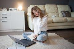 Conversazione bionda sveglia sul telefono che si siede sul pavimento Lavoro con un computer portatile, blogger indipendente Immagini Stock