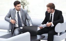 Conversazione degli impiegati, sedentesi l'ingresso dell'ufficio Immagini Stock