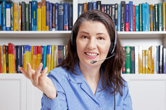 Conversazione dei libri di ufficio della cuffia avricolare della donna Fotografia Stock Libera da Diritti