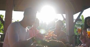 Conversazione del gruppo della gente che mangia prima colazione e che beve mattina di Juice On Summer Terrace In, amici della cor archivi video