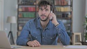 Conversazione del telefono, giovane che assiste alla chiamata sul lavoro archivi video