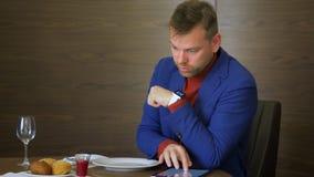 Conversazione dell'uomo di affari dalla viva voce in orologio e compressa astuti usando in ristorante stock footage