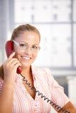 Conversazione di funzionamento del receptionist grazioso sul telefono Immagini Stock