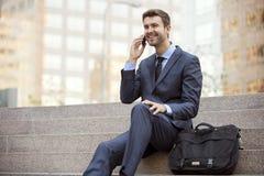 Conversazione di seduta dell'uomo di affari sul telefono cellulare Fotografia Stock Libera da Diritti