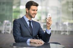 Conversazione di seduta dell'uomo di affari sul telefono cellulare Immagini Stock