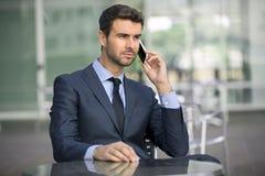 Conversazione di seduta dell'uomo di affari sul telefono cellulare Fotografie Stock