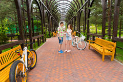 Conversazione di una ragazza e di un tipo con le bici in arco Fotografie Stock Libere da Diritti