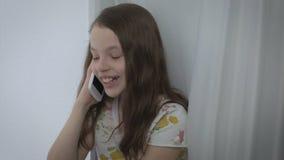 Conversazione emozionale della bella bambina sullo smartphone e ridere stock footage
