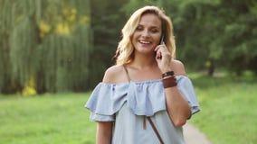 Conversazione femminile allegra sul telefono che cammina nel parco