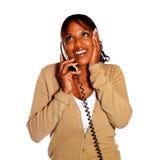Conversazione femminile emozionante sul telefono ed osservare in su Fotografia Stock