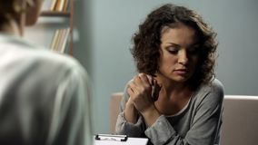 Conversazione femminile triste con suo psicoterapeuta alla riunione personale, sensibilità ansiosa fotografia stock