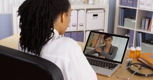 Conversazione paziente nera con medico sopra video chiacchierata del computer portatile fotografie stock