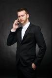 Conversazione scettica dell'uomo d'affari seria sullo smartphone Fotografia Stock