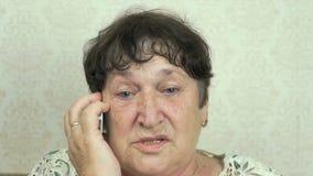 Conversazione senior dello smartphone della tenuta della donna a medico stock footage