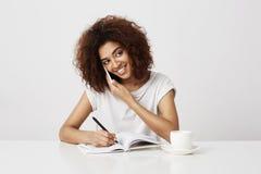 Conversazione sorridente della donna di affari africana sul telefono nel luogo di lavoro Priorità bassa bianca Immagine Stock