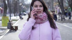 Conversazione telefonica, donna felice che parla sul cellulare mentre camminando sulla via