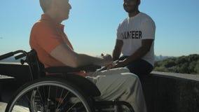 Conversazione volontaria allegra con un uomo wheelchaired stock footage