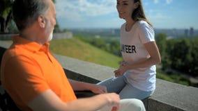 Conversazione volontaria del positivo con un uomo wheelchaired all'aperto video d archivio