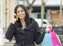 Conversazione wonan sorridente dal telefono e tenere i sacchetti della spesa. Fotografia Stock Libera da Diritti