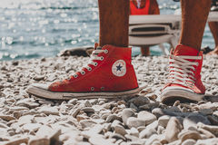 Converse sneakers on the beach. Converse sneakers on a beach of pebbles near the sea Stock Photo