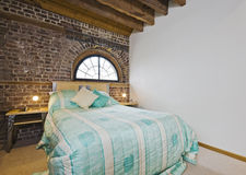 Conversion apartment. Bedroom of a warehouse conversion apartment with exposed brick works stock photo