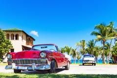 1956 convertível vermelho americano e um carro 1956 branco azul do vintage estacionaram direto na praia dentro imagem de stock royalty free