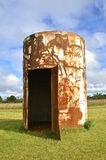 Converted rusty oil barrel into yard storage shed Royalty Free Stock Photo