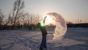 Convertendo a água quente no vapor, frio extremo -30 -35 graus O homem derrama um copo da água quente no ar, a água vídeos de arquivo