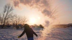 Convertendo a água quente no vapor, frio extremo -30 -35 graus O homem derrama um copo da água quente no ar, a água filme