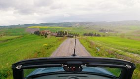 A convertible car rides on a gravel road. View from the roof. Mid shot stock video footage